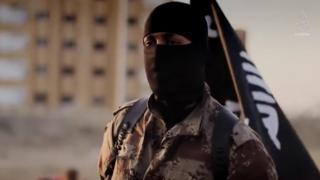 Masked Islamic State militant near 17th Division base in Raqqa province, Syria