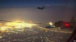 A handout photo taken 5 October 2014 and obtained on 9 October shows two Royal Australian Air Force (RAAF) F/A-18F Super Hornet aircraft refuelling from a RAAF KC-30A Multi Role Tanker Transport aircraft above a city in Iraq.
