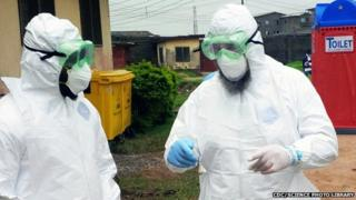 Doctors wearing personal protective equipment outside an Ebola treatment unit