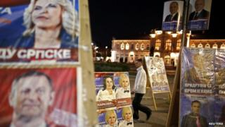 Man walks past election posters