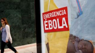 "A woman walks past a bus stop banner reading ""Emergency Ebola"" near Madrid, Spain. Photo: 9 October 2014"