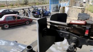 Iraqi policemen search a car at a checkpoint in Baghdad, Iraq, on 11 October 2014.