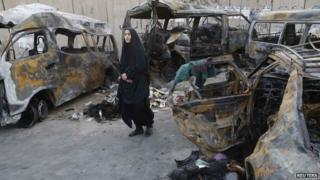 A woman looks at vehicles destroyed in a car bomb attack in the Shaoula neighbourhood of Baghdad October 12, 2014