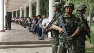 """Paramilitary policemen stand guard during a ceremony to award those who the authorities say participated in """"the crackdown of violence and terrorists activities"""" in Hotan, Xinjiang Uighur Autonomous Region 3 August 2014"""