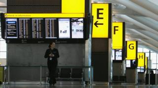 A member of staff stands in the Check-In area of Terminal 5 at Heathrow