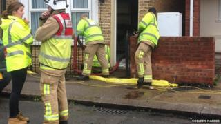 Helen Williams with the firefighters that pumped out flood water that ruined her kitchen floor and white goods