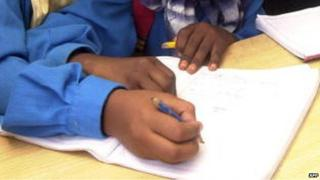 Somali girls write during a class session in the UN High Commissioner for Refugees (UNHCR) camp in Kharaz, Yemen, on 25 April 2006