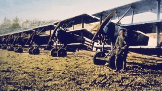 A German soldier stands by a row of Fokker DR-1 tri-planes on an airfield in Germany