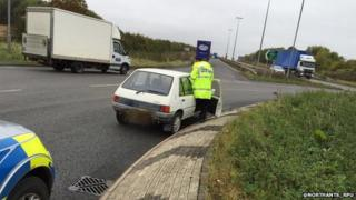 Abandoned Peugeot 205 on a roundabout in