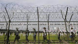 South Korean army soldiers patrol through the military wire fences with hanging South Korean national flags at the Imjingak Pavilion near the border village of Panmunjom, which has separated the two Koreas since the Korean War, in Paju, South Korea, on 17 September 2014