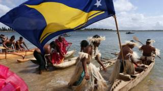 Traditionally dressed representatives from South Pacific nations push their canoes into the water as they prepare to participate in a protest aimed at ships leaving the Newcastle coal port, located north of Sydney October 17, 2014.