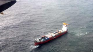 A Canadian Coast Guard helicopter flies near a Russian container ship