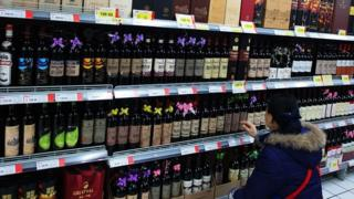 A woman looks at wine in a supermarket in Hubei, China (Feb 2014)