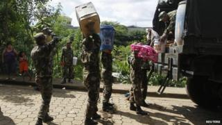 Nicaraguan Army personnel carry belongings from residents displaced by heavy rains, which caused flooding and landslides in the capital Managua Oct 18 2014