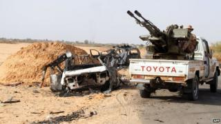 """Fighters of Libya""""s Fajr Libya (Libyan Dawn) drive their pick up truck mounted with a machine gun near a burnt car, south of the town of Wershfana on October 13, 2014"""