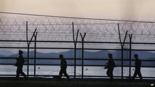 South Korean army soldiers patrol through the wire fences near the demilitarised zone between the two Koreas in Paju, South Korea, 7 October 2014
