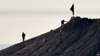 Alleged Islamic State militants stand next to a black IS flag near the Turkish-Syrian border