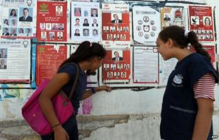Tunisian girls look at election posters put up on a street ahead of the parliamentary election in the Tunis suburb of Ariana on October 21, 2014.