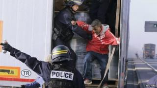 French riot policemen force out migrants in Calais, France on 22 October 2014