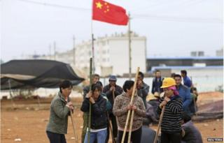 Villagers guard the entrance to Fuyou village next to the Chinese national flag in Jinning county, Kunming, Yunnan province 15 October 2014
