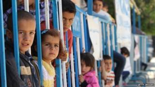 Syrian refugee children wait to be registered at a refugee camp in Bar Elias, in the Lebanese Bekaa valley on 30 May 2014
