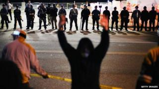 A protestor raises his hands in front of police during demonstrations in Ferguson, Missouri, on 22 October.