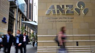Pedestrians walk past the entrance to the Australia and New Zealand Banking Group (ANZ) building