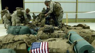 US Marines arrange their equipment as US troops arrive in Kandahar after their withdrawal from the Camp Bastion in Afghanistan on 26 October 2014
