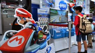 Customers play with Nintendo's videogame console Wii U at an electronics shop in Tokyo.