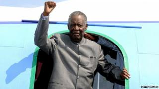 Michael Sata gestures upon arrival at Solwezi airport before addressing supporters at an election campaign meeting in September