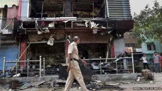 A policeman walks past a burnt shop in Trilokpuri, New Delhi