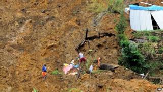 Sri Lankan residents search the site of a landslide caused by heavy monsoon rains in Koslanda village in central Sri Lanka on October 30, 2014.
