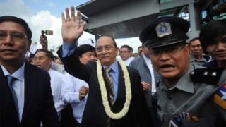 October 1, 2012, Myanmar President Thein Sein (C) greets supporters as he arrives at Yangon International Airport