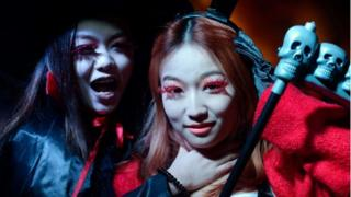 Women in costumes pose while revellers celebrate Halloween in Beijing on October 31, 2013