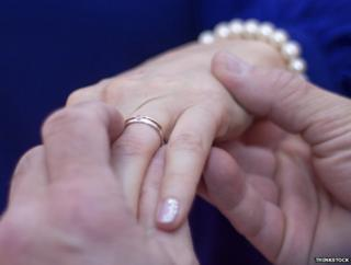 Man's hands putting ring on woman's finger