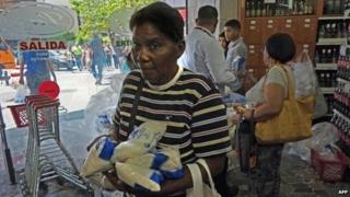People shop at a supermarket in Caracas on 29 October, 2014