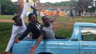Three people leaning out of a truck with their arms outstretched