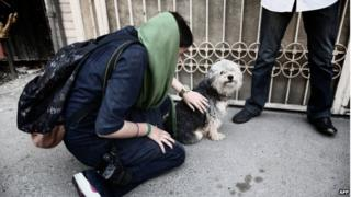 A woman pets her dog on a street in Tehran