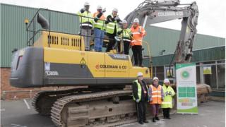 Greencore workers standing on and in front of a digger