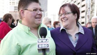 Jayne Rowse (L) and her partner April DeBoer speak with the news media while attending a rally in favor of same-sex marriage at the U.S. Courthouse 16 October 2013