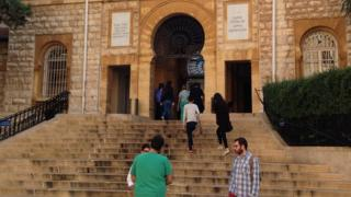 Students chat on the steps by the main entrance