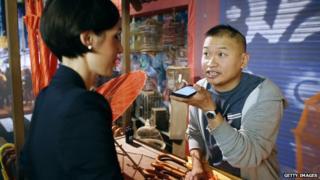 Man talking to a woman via his Google translate phone