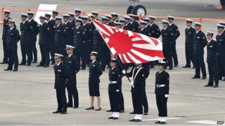 Navy servicemen of the Japan Self-Defense Force stand with their flag prior to a review ceremony on a runway at the Japan Air Self-Defense Force's Hyakuri air base in Omitama, Ibaraki prefecture on 26 October 2014.