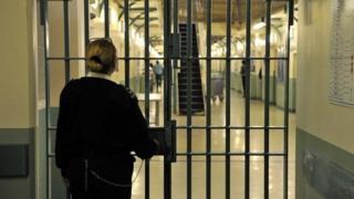 A prison officer locks a door at Wormwood Scrubs prison