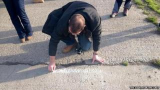 Man covers graffiti in chalk