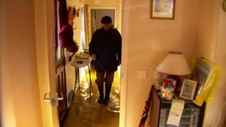 Brendan McCann walks through his flooded home in Portadown
