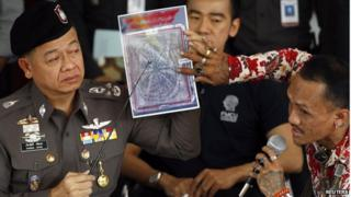 A tattoo expert and a policeman (L) point at one of the pictures of body parts found in parcels as they address reporters in Bangkok 17 November 2014