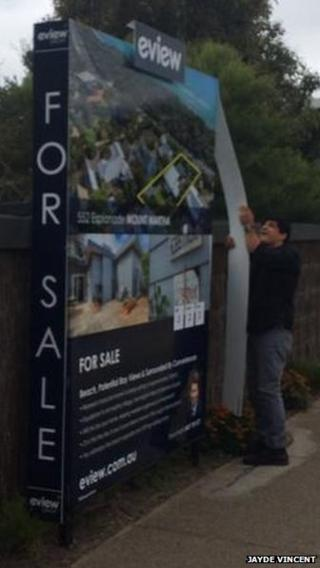man removing sign