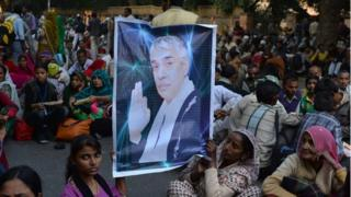 """Devotees of Indian self-styled """"godman"""", Rampal Maharaj hold a poster of his image during a dharna - non-violent sit-in protest"""
