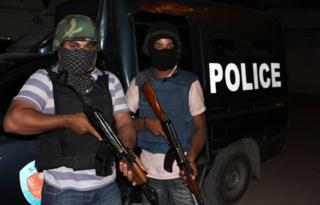 Masked and armed police officers next to a police van in Karachi preparing for a raid